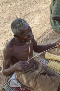 Abugre Abentarah splitting straw. He will, then roll the two strands together making a pliable rope that is used for weaving.
